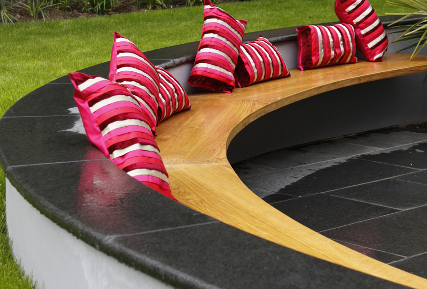 a circular cantilevered bench used for a social space in this greencube garden in tunbridge wells, kent