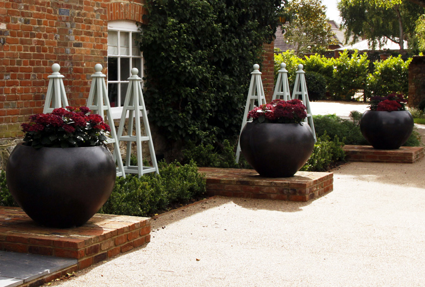 thoughtful pladement of repeating large pots create focal points and contrasts in this lutyens inspired front garden in sevenoaks, kent by greencube garden design