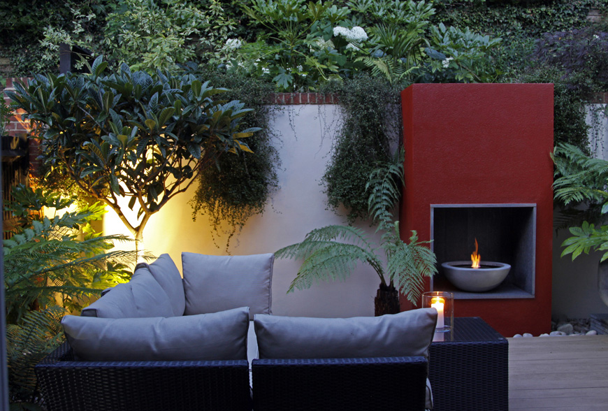 In this greencube garden design in caterham, surrey uplighting specimen trees adds a wonderful ambience to the garden