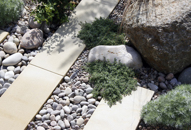 boulders, pebbles, plank paving and drought tolerant planting combine in this city garden design in chislehurst, london