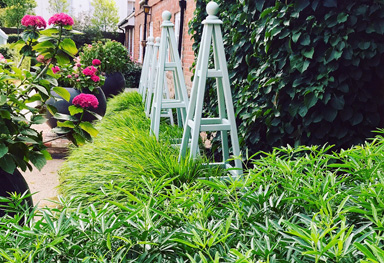 painted wooden obelisks create a focal point within the simple planting of this lutyens inspired front garden design in sevenoaks, kent