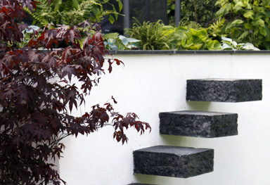 canitlevered basalt steps in a rendered wall enable occasional access to the top of the garden design in loughton, essex