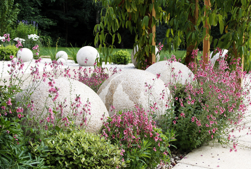 yellow granite sculptural balls contrast with pink and purple planting scheme in this garden design in crouch, kent