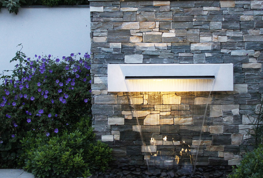 nordic cladding and rendered retaining walls for textural contrast with an underlit water blade feature are used in this garden design in sevenoaks, kent