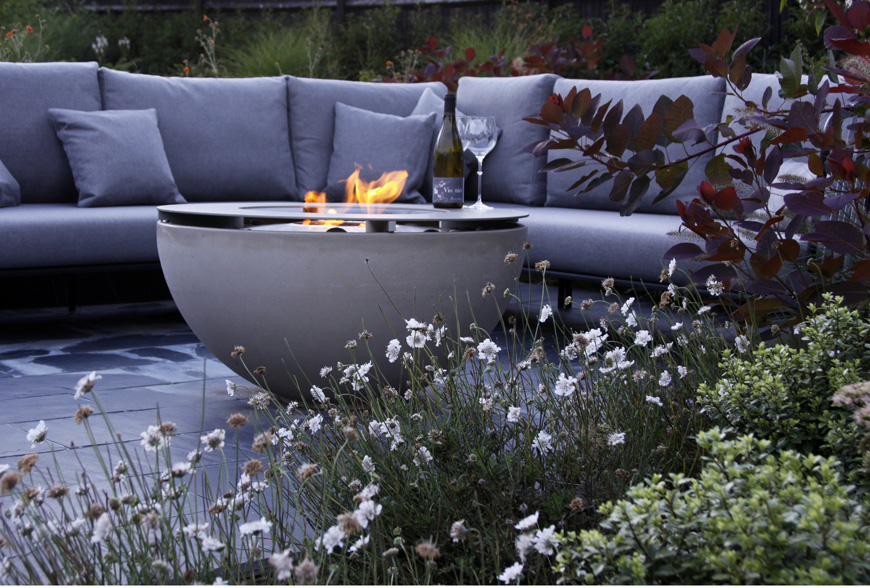 a contemporary garden in Westerham, Kent featuring a firebowl and comfy seating softened and surrounded by a modern planting palette